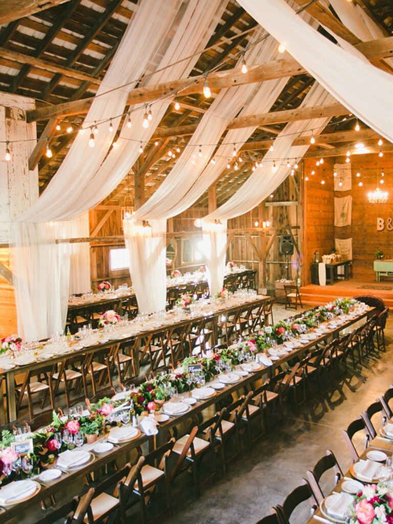 Rustic barn reception space with draped white fabric decor