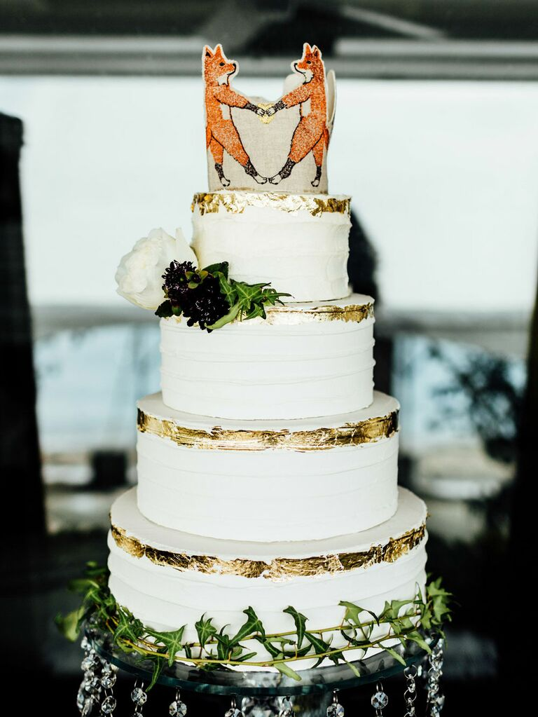 Rustic wedding cake topper with foxes holding hands at barn wedding