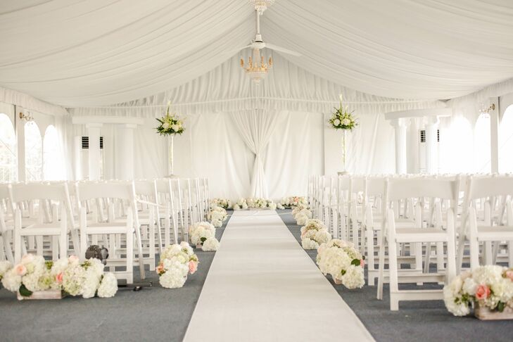 """""""Since most of our guests were coming from out of town, I knew I wanted to play up the beautiful, sunny, green spring tones Florida would offer,"""" says Alina. With a little help from Simply Divine Events, the couple accented their tented ceremony with chandelier lighting, white folding chairs, white columns and a few lush florals. Jennie's Flowers lined the aisle with white hydrangeas, pink roses, green hydrangeas and greenery to note Florida's natural beauty."""