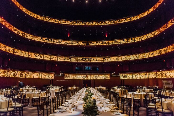 To go with the dramatic performance hall, Millie and Luke had a center head with 50 guests, surrounded by smaller round tables. The tables were covered with light pink cloths,  runners of seeded eucalyptus and elegant gold accents. Every seat included a menu what was at the dinner stations.