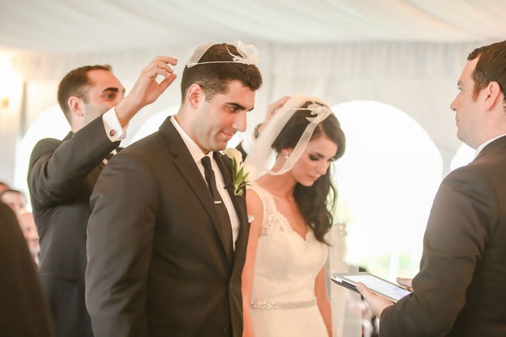 """Alina and Nick chose to have their ceremony and Greek Orthodox stefana crowning tradition under a classic white tent at Safety Harbor Resort and Spa. """"Even though we weren't getting married in the Greek church, we wanted to intimacy churches offer,"""" says Alina. The couple lined their ceremony with all white florals as 125 friends and family members watched from rows of white chairs."""