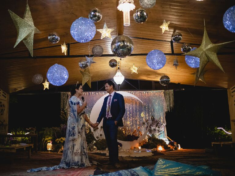 Bride and groom making speech under hanging star accents and illuminated disco balls at celestial wedding