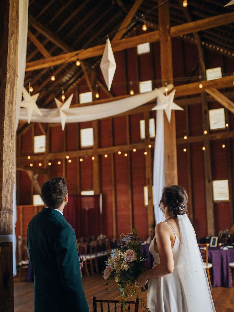 Bride and groom looking up at suspended stars at celestial wedding