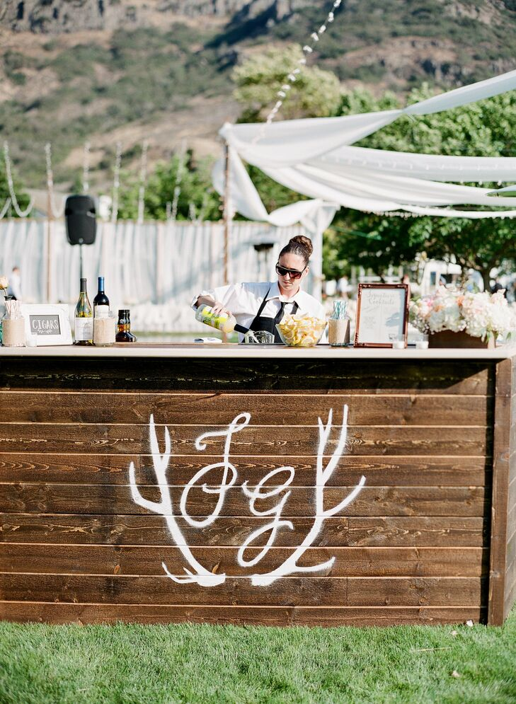 The couple painted the wooden cocktail bar with the same monogram that appeared on their invitations.