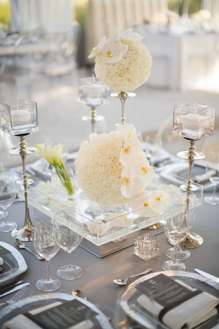 All-white arrangements of hydrangeas and phalaenopsis orchids served as centerpieces, while the same blooms were used to cover Whitney and Matt's cake pedestal.