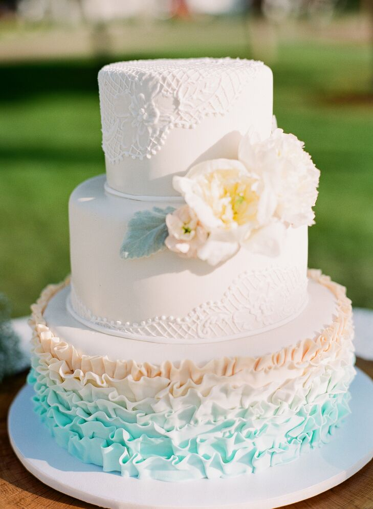 The bottom of the three-tier wedding cake was decorated with blue ombre ruffles. The top two layers had a more classic look with ivory fondant and lace piping.