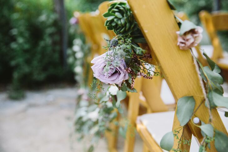 Garlands of roses, eucalyptus and succulents adorned the back of wooden folding chairs during the outdoor ceremony.