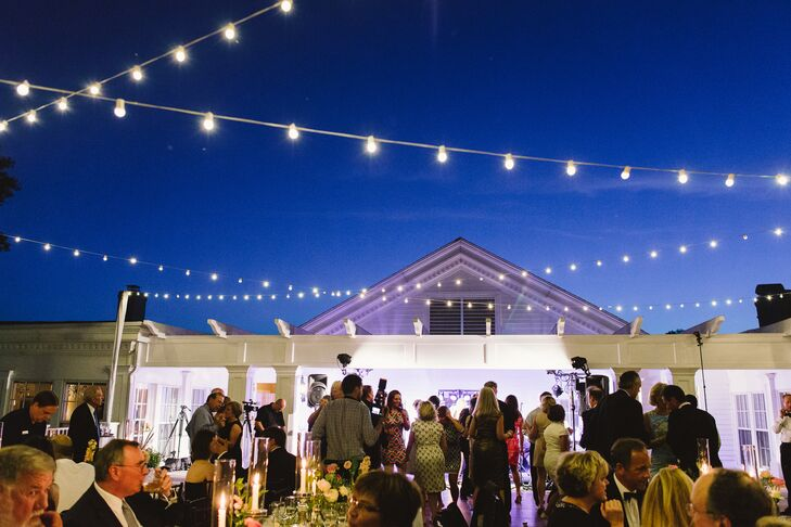 """Katie was set on the idea of having string lights below a starry sky over the dance floor. """"I will never forget seeing the tables and lights all set up on the deck overlooking Lake Calhoun with the Minneapolis skyline in the background. It was magic!"""" says the bride."""