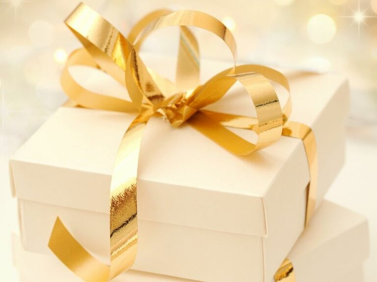 white gift box wrapped in gold ribbon