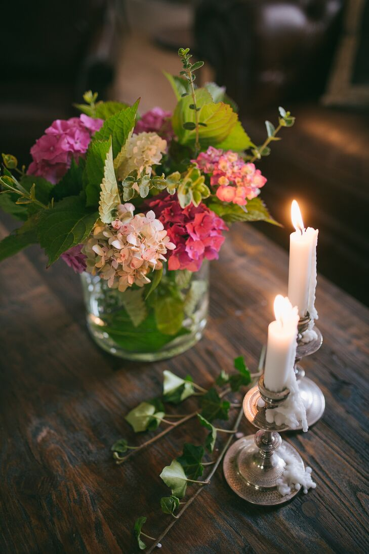 The tables were decorated with pink hydrangeas and ivy garlands for a garden feel. They added candlesticks in silver candelabras for a romantic touch.