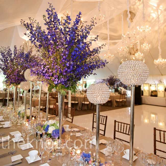 Tall vases filled with blue delphiniums added height to the tables, and alternating blooms with crystal globes was an elegant touch.
