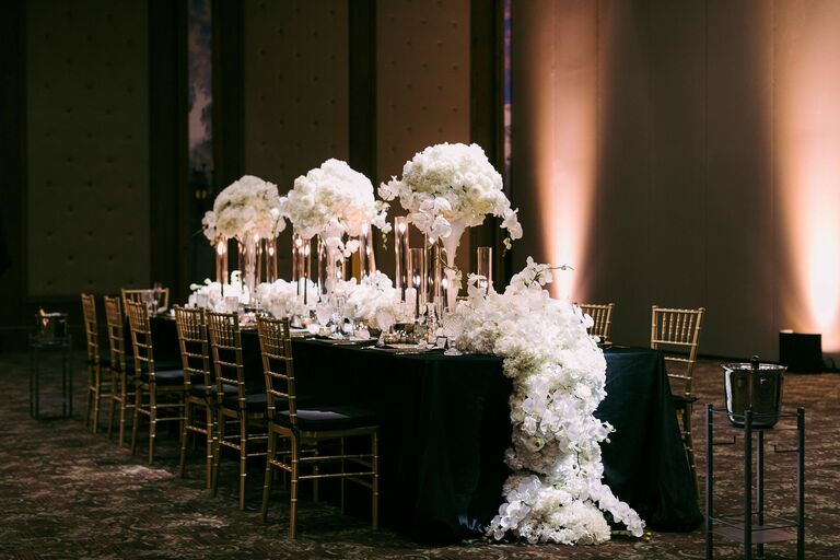 Reception table with floral runner and tall floral centerpieces