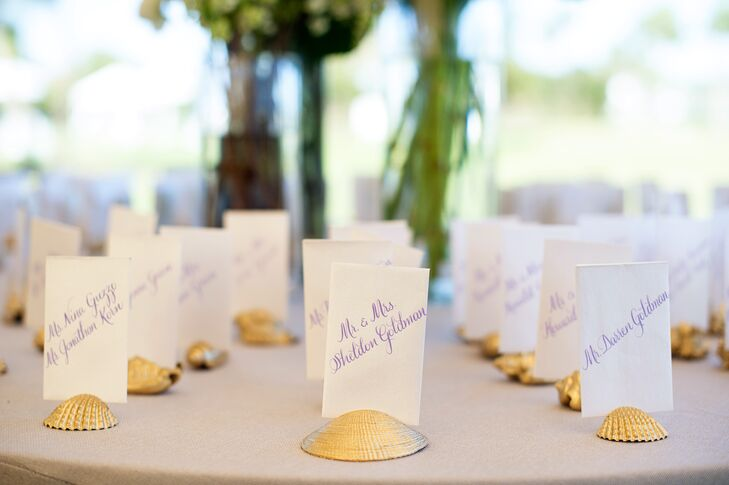 """As a nod to the locale, Emily and Jason displayed their escort cards in gilded seashells. """"I love watercolors, so we had watercolor artwork by Carly Martin of Clementine Studio integrated into our day-of items,"""" Emily says."""