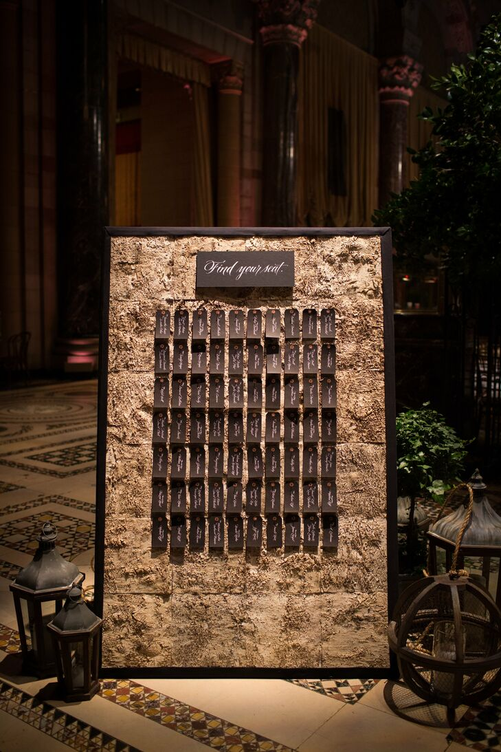 """""""I knew that I didn't want classic folding cards,"""" Leigh recalls of the escort card display. Instead, they used a custom board covered in birch wood that created a """"rustic winery feel."""" Individual black tags finished the look."""