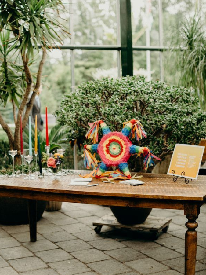 piñata guest book on wood farm table in greenhouse