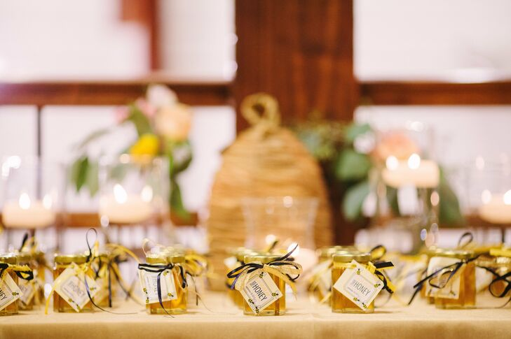 """Jars of honey tied with navy and yellow ribbon that said """"Sweeter Than Honey"""" were the favors."""