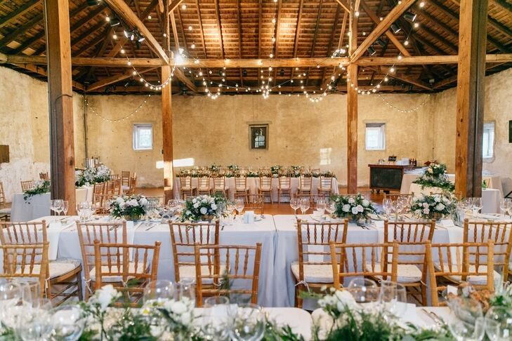 Inside the grounds' 19th-century stone barn, several large farm tables were arranged under romantic string lights. A number of floral arrangements featuring greenery and white roses lined each table.