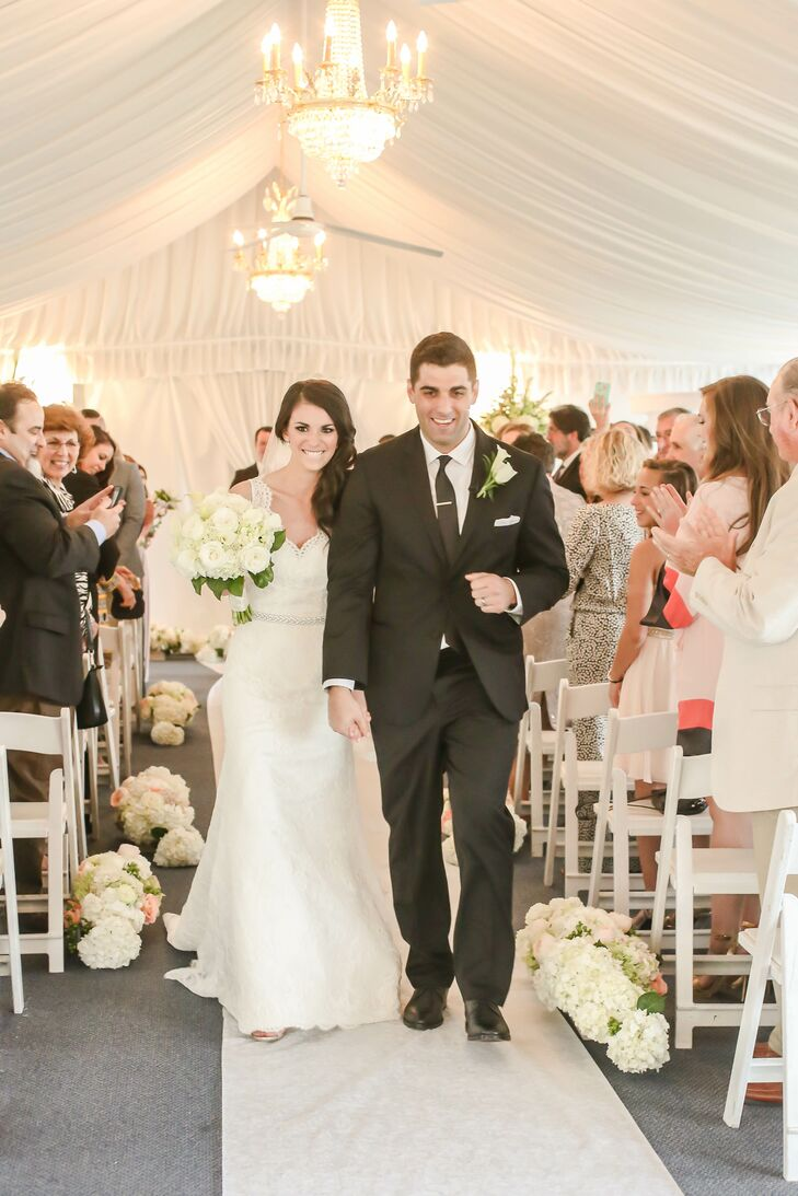 After a trip to Men's Wearhouse, Nick and his groomsmen were dressed in classic black Vera Wang tuxedos for the tented ceremony. Nick stood out with a double white calla lily and rose boutonniere that complemented Alina's bouquet. Her arrangement also included white hydrangeas and a touch of greenery.