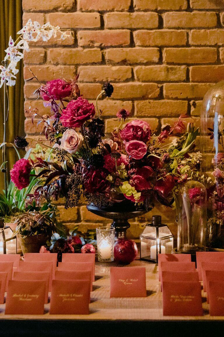 Letter and envelope escort card display with large floral arrangement