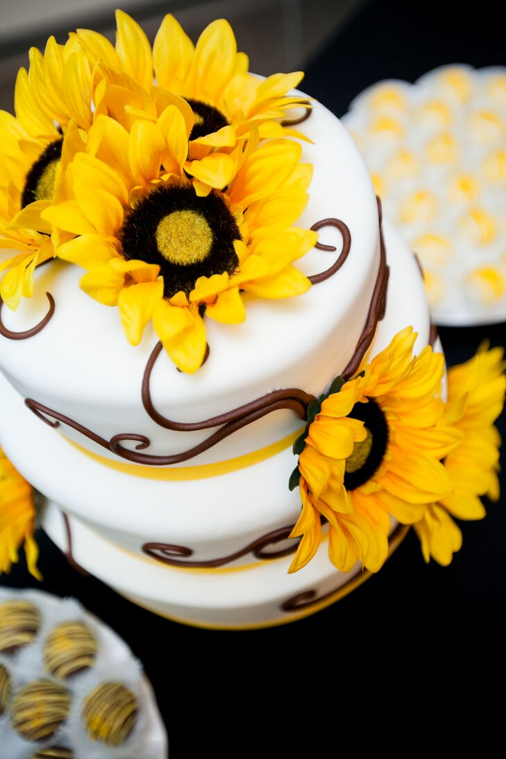 The three-tier wedding cake was decorated with brown piping, yellow ribbon and sunflowers. The cake had a different flavor for each tier.