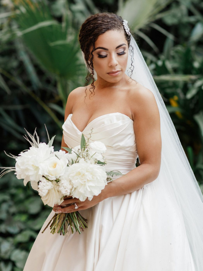 Bride with updo and veil holding white bouquet