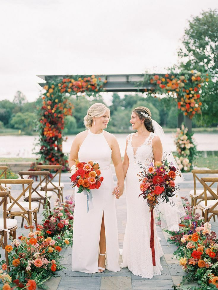 Two brides holding red bouquets