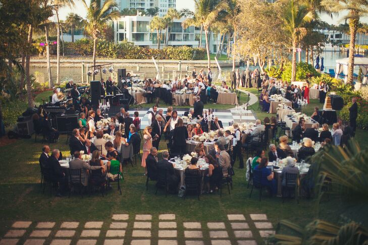 """The couple decorated their outdoor garden reception with glass-topped round tables, gold linens, black chiavari chairs, a black and white checkerboard dance floor, string lighting, Great Gatsby-inspired art deco table numbers and gold accented floral centerpieces. """"It was a magical and enchanted night for all,"""" says Amina."""
