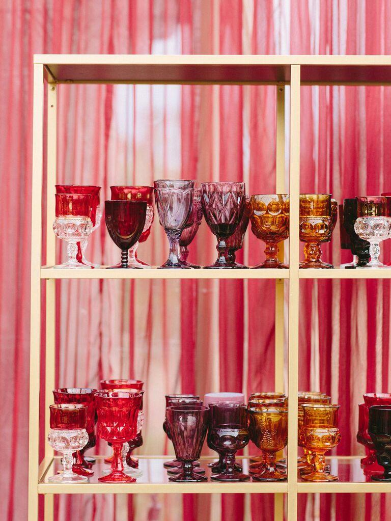 Mismatched jewel-toned glassware at wedding reception bar
