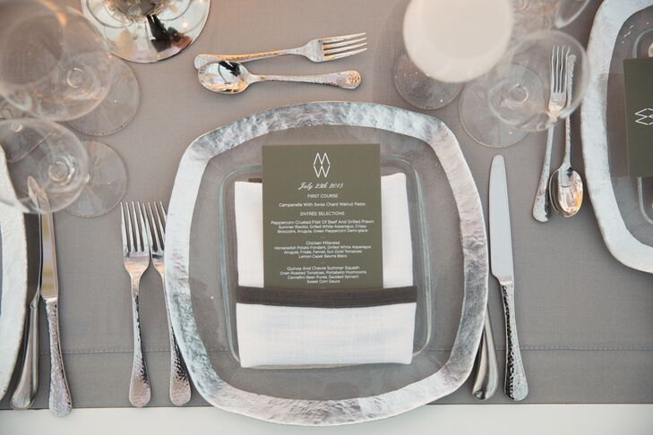 Tables were topped with silver-rimmed dinner plates, glass votives and arrangements of white orchids.