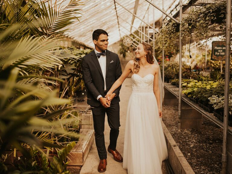 Bride and groom walking through greenhouse