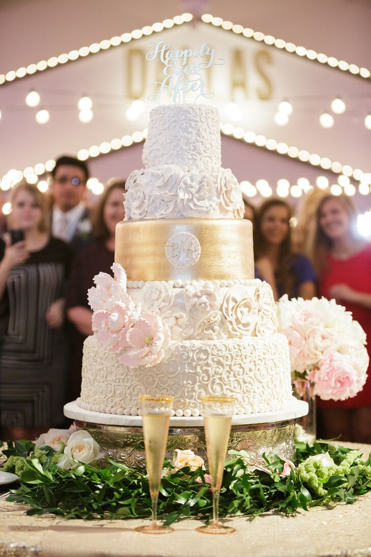 """This five-tiered wedding cake by Frosted Art is simply breathtaking. Tiers of intricate details, flower rosettes and even a single metallic gold tier with Blair and Alex's monogram ties the confection to everything about their wedding. Blush sugar flowers, the newlyweds' monogram and a """"Happily Ever After"""" cake topper complete the cake."""