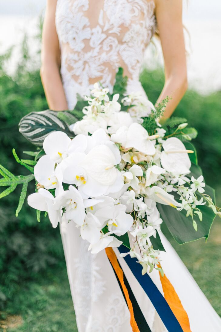 """Florist Lauryl Lane created elegant compositions using the beautiful exotic flowers—like white orchids—and lots of greenery. """"We used all local grown tropical flowers. Ginger, ferns and orchids were just a few of our favorites,"""" says Evgeniya."""