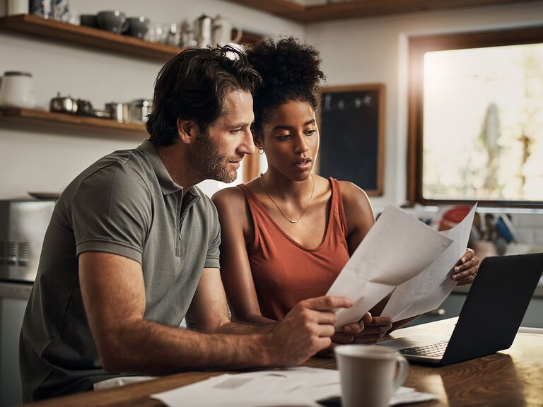 couple looking at papers sitting in kitchen