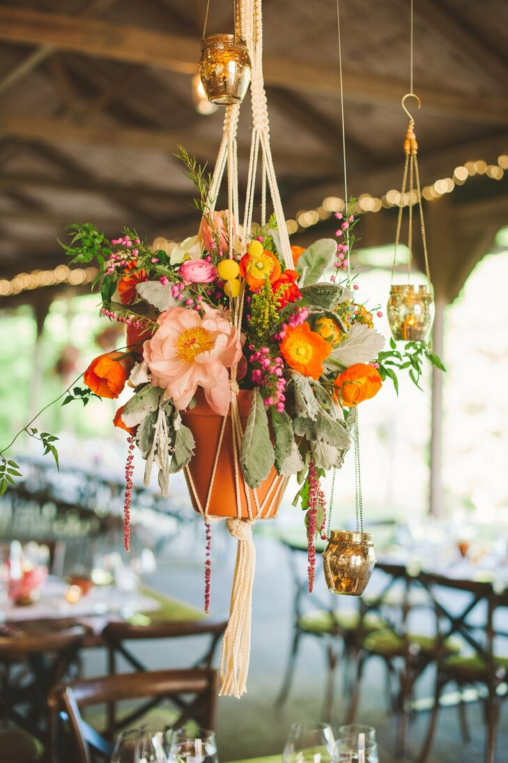The couple mixed pink, orange, yellow and green flowers in macramé hanging arrangements surrounded by mercury glass to add color to the rustic reception.