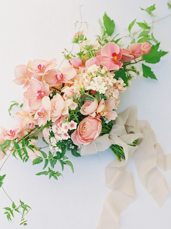 Peach-hued orchid bouquet with ribbon