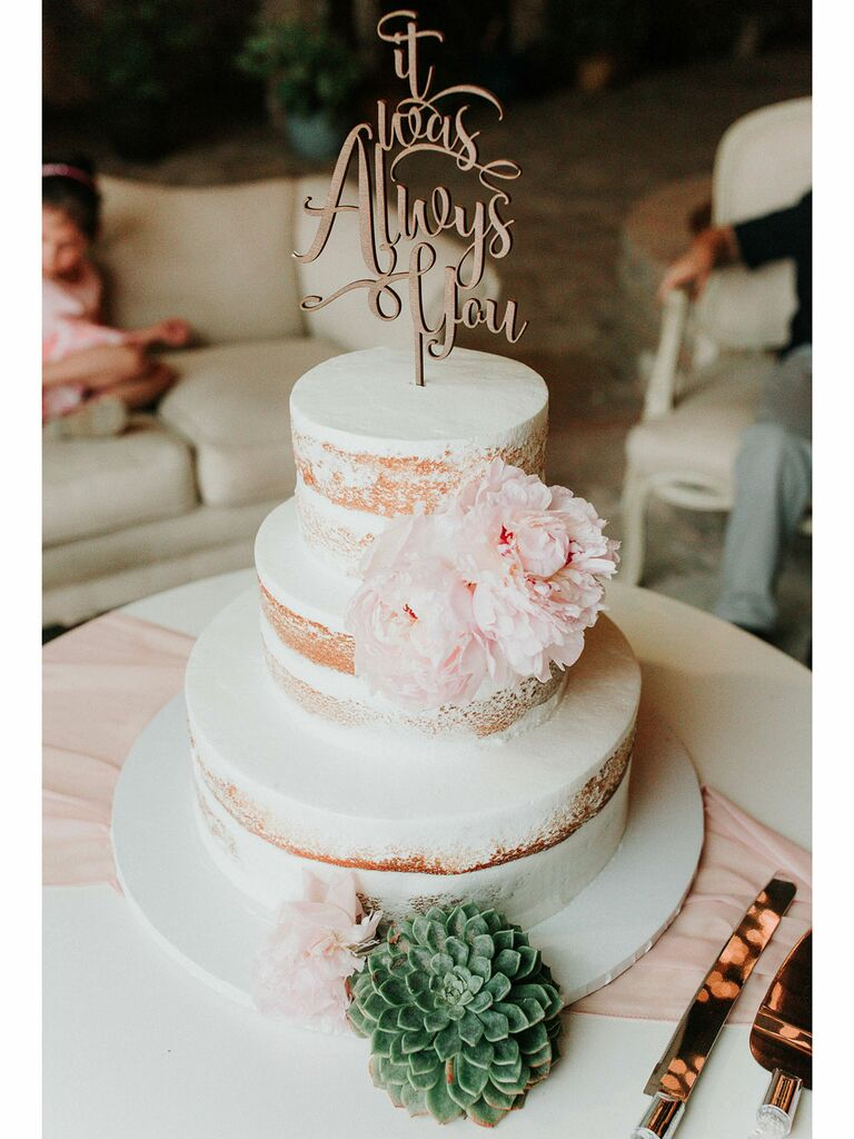 Semi-naked rustic wedding cake with white icing and pastel peonies with succulents
