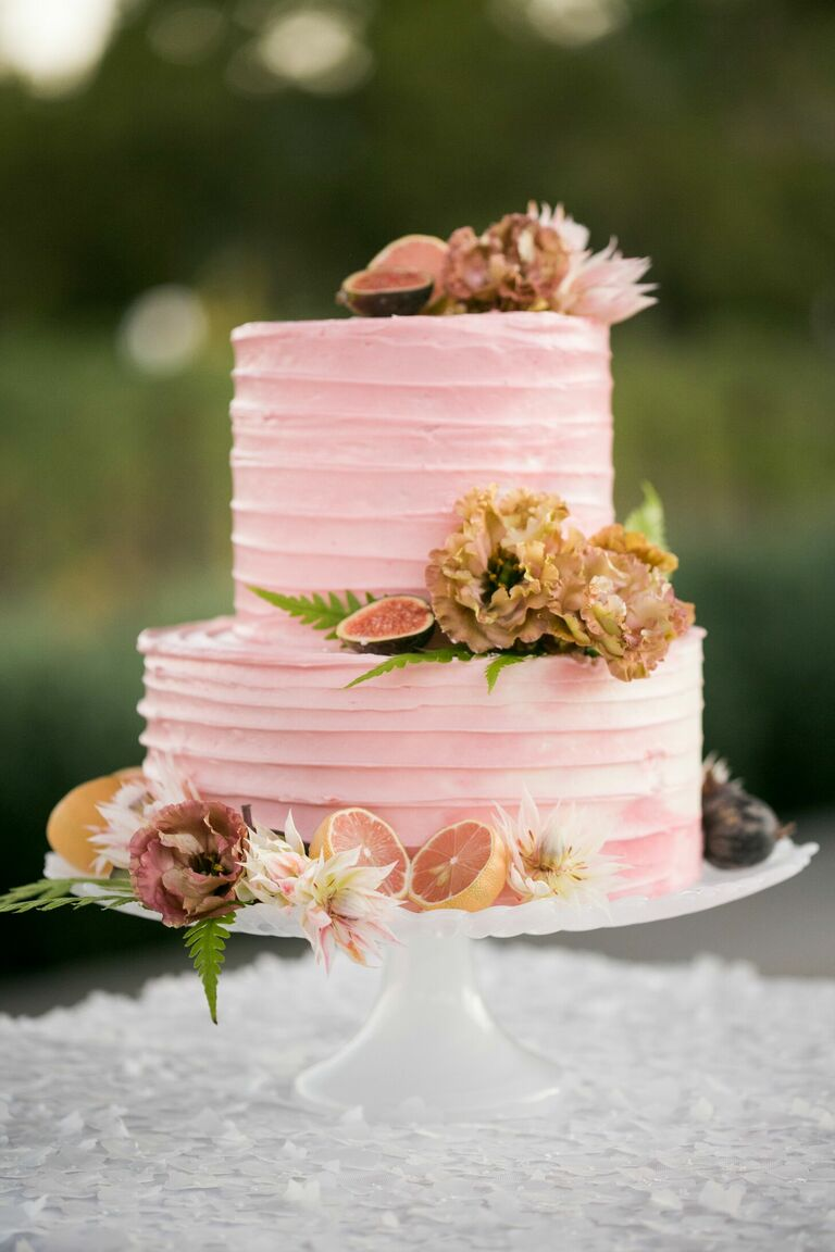 Two-tier pink cake with fresh fruit decorations