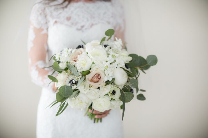 Genevieve's bouquet was ever evolving throughout the planning process. Fiore Fine Flowers worked with the bride-to-be to create a stunning, romantic arrangement filled with silver dollar eucalyptus, peonies, roses, anemones, baby's breath and stock flowers in shades of ivory, white and blush.