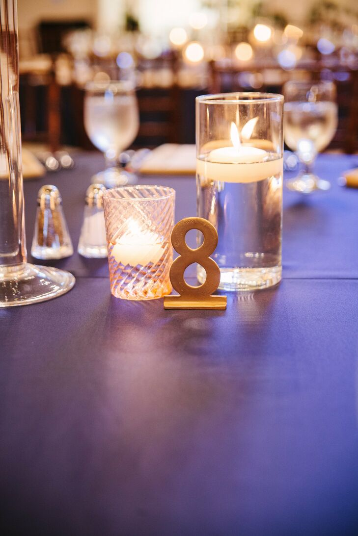 Each table number was painted gold. Other decorations on the table included floating candles in different sized vases.