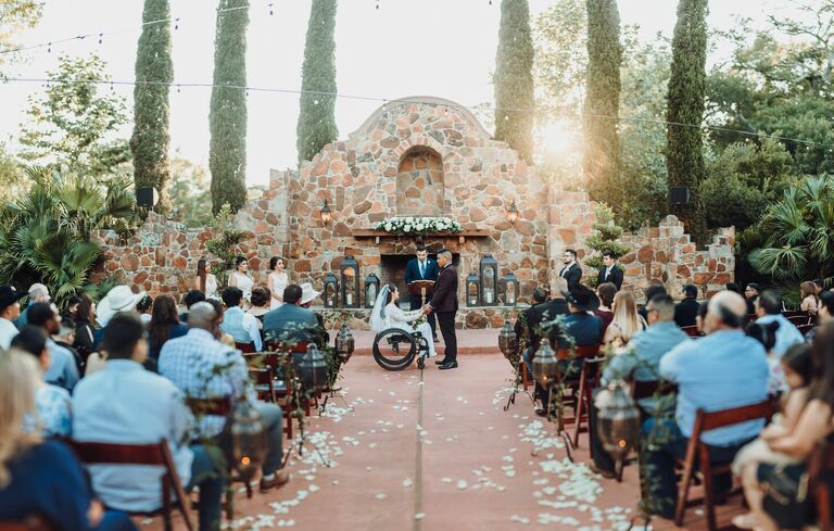 Outdoor wedding ceremony with stone backdrop