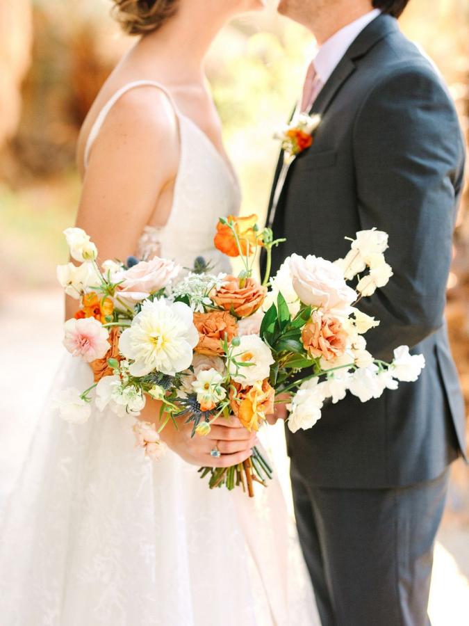 Couple holding white-and-orange wedding bouquet