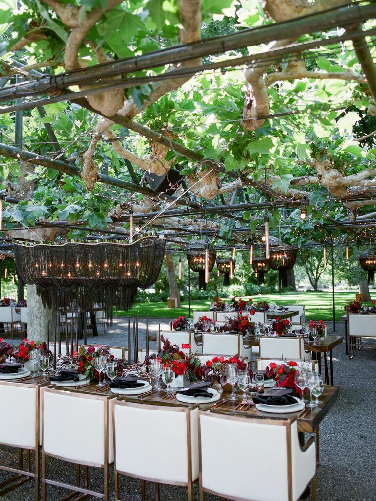 Outdoor modern wedding reception with lowered black macrame chandeliers and candles
