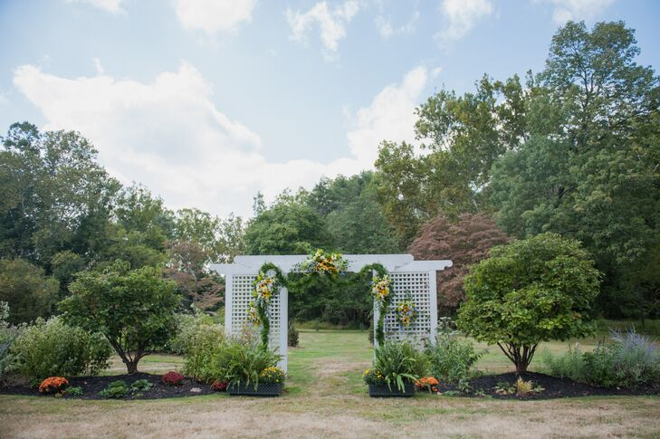 """""""We visited the Woolverton Inn for a romantic weekend getaway and fell in love with the place and the surrounding area,"""" Caitlin says. """"The night we got engaged, we both agreed it was a no-brainier to have our wedding there."""" Caitlin and Sean highlighted the inn's grounds and chose limited decor for the outdoor ceremony. Instead, a white wedding arch was covered with natural greenery, roses, sunflowers and orchids from Mark Bryan Designs."""