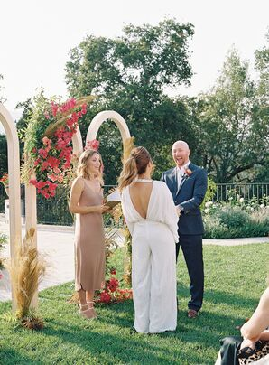 Bride and Groom Exchanging Vows Beside a Triple Wedding Arch