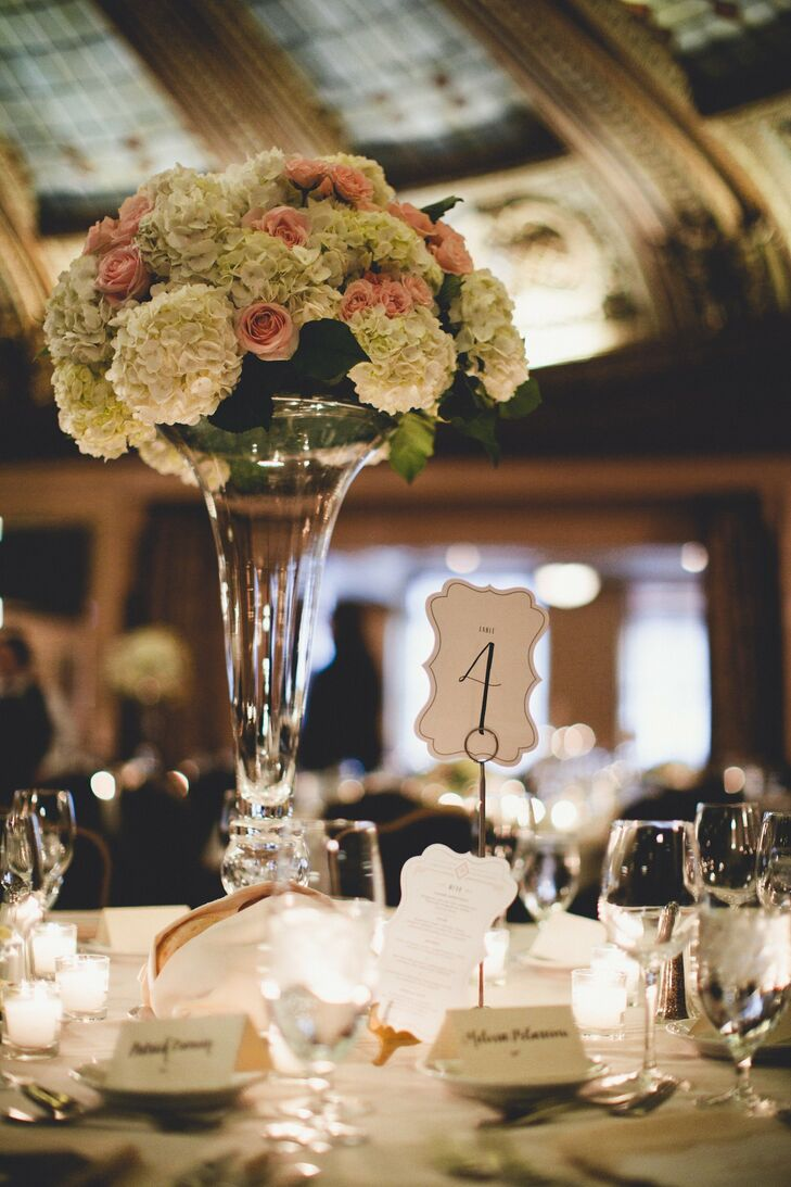 White hydrangeas mixed with light pink roses filled tall trumpet vases for formal centerpieces during the reception.