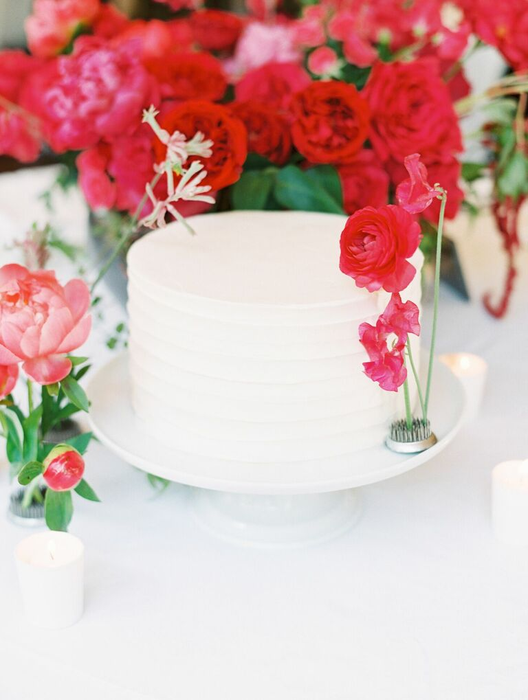 Single-tier white cake with pink fresh flower accents
