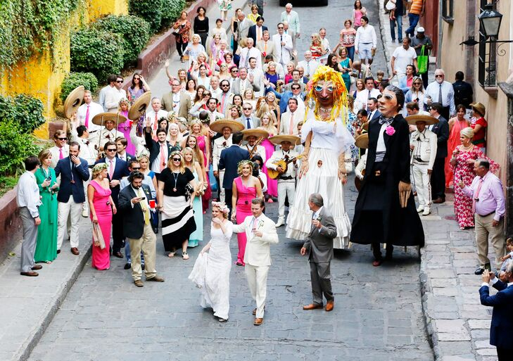 The traditional San Miguel de Allende recessional parade with mojigangas was an experience like no other for Louisa and Joseph's 160 wedding guests. They paraded through the streets of San Miguel de Allende with larger-than-life papier-mache mojigangas and tequila shot glasses around their necks, which they could fill with tequila carried by a donkey!