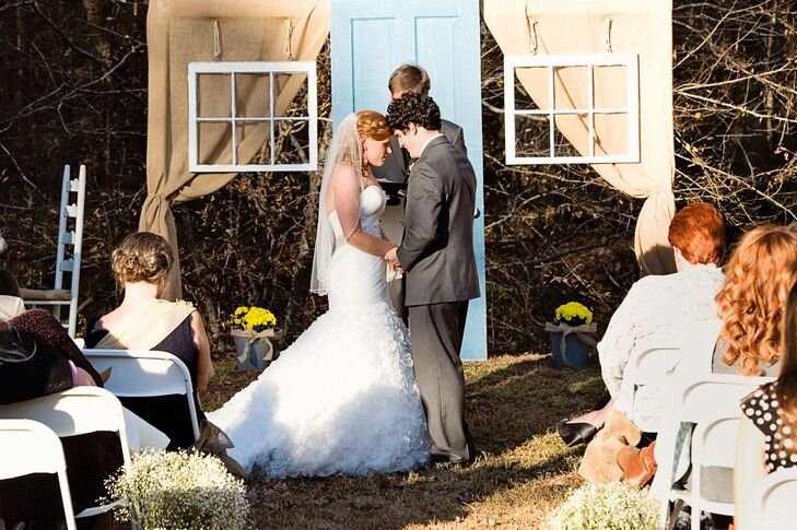 The couple used an old door and windows from Kristy's grandfather's house to create a homey ceremony backdrop.