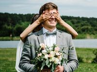Bride covering groom's eyes during first look on wedding day