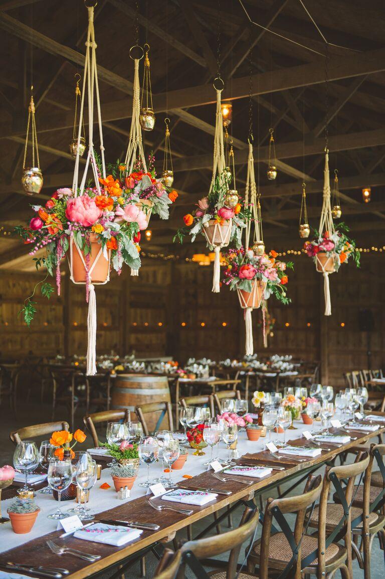 Suspended floral arrangements in barn wedding reception